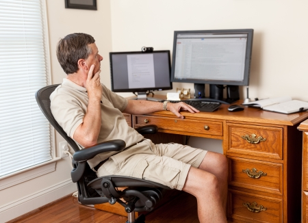 Managing remote teams - a man working from home in shorts with desk with two monitors