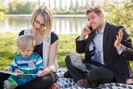 Three signs you're addicted to work - a father is talking business on his phone while at a picnic with his young family