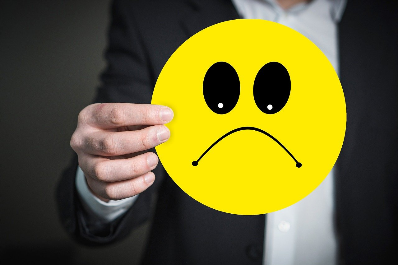 How to rebuild trust after a bad online review - a man holds an unhappy emoticon picture.