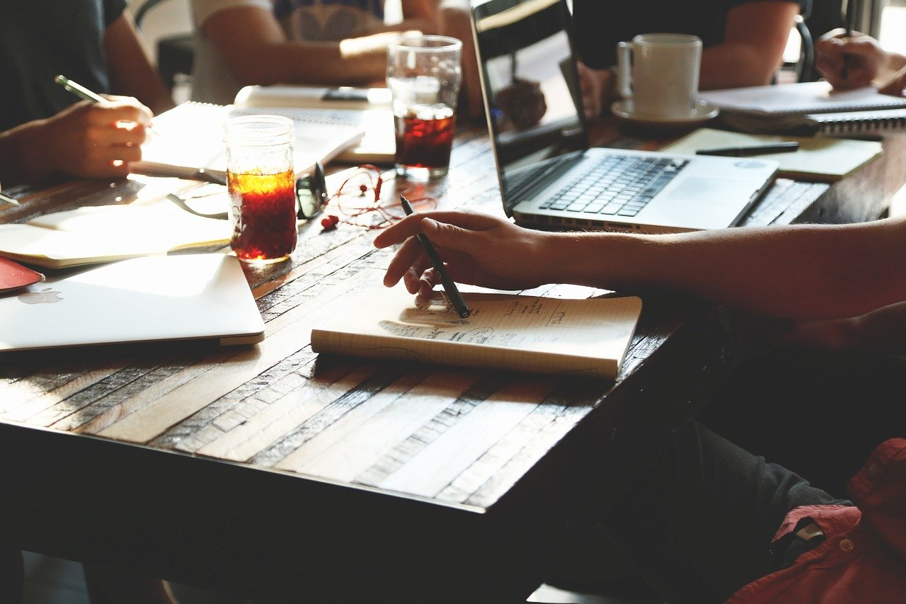 Small business EOFY planning tips - business people sit around a table with papers, computers and coffee