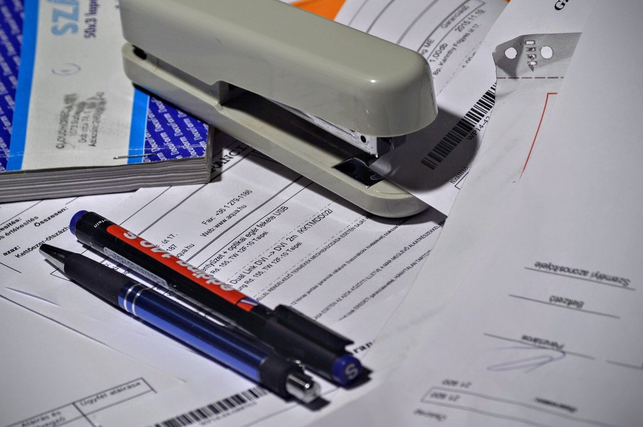8 things your invoice needs in order to get paid faster - an invoice book and various items of stationery scattered on a desk.