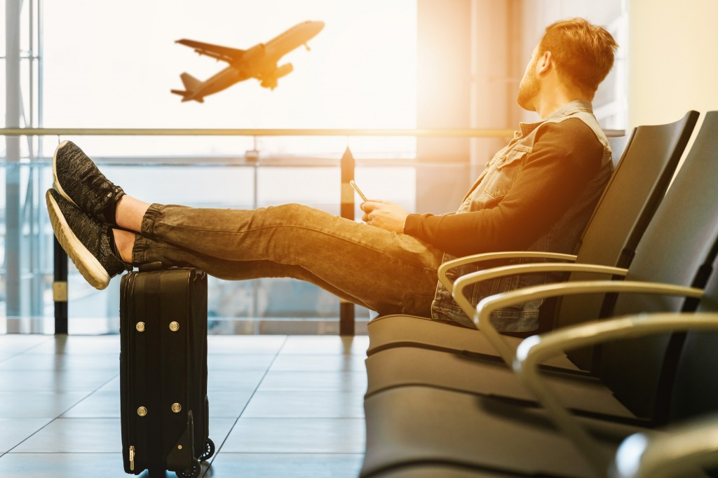 4 tips for less stressful business travel - a young man at airport with his feet up on his luggage watches a jet taking off in the morning sun