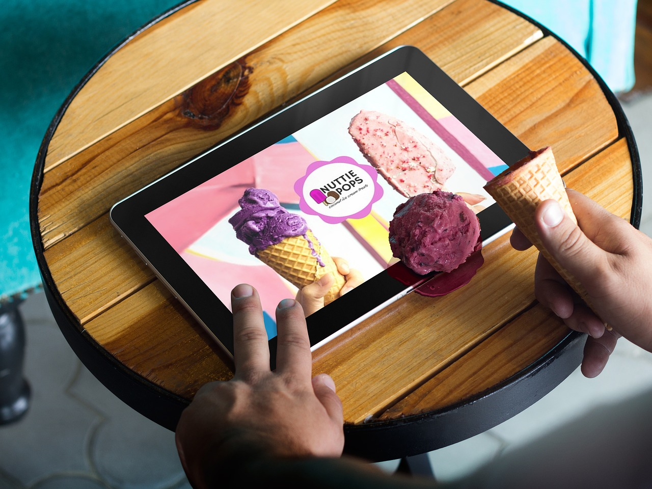 Five Simple Marketing and Promotion Tips to help during COVID-19 - A tablet user drops their ice cream onto a digital advertisement for the ice cream