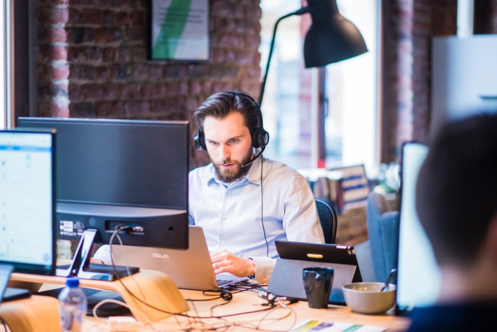 10 tips to reduce debtor days for small business owners - man wearing headset in front of computer