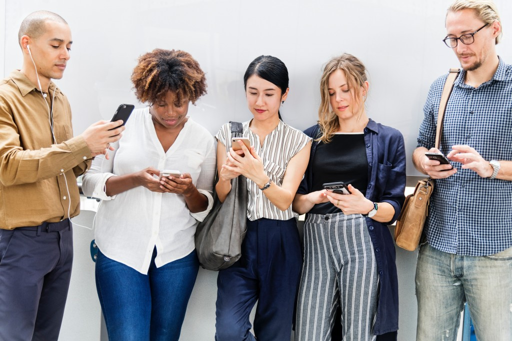 Boosting social proof - photo of a group of people looking at their phones
