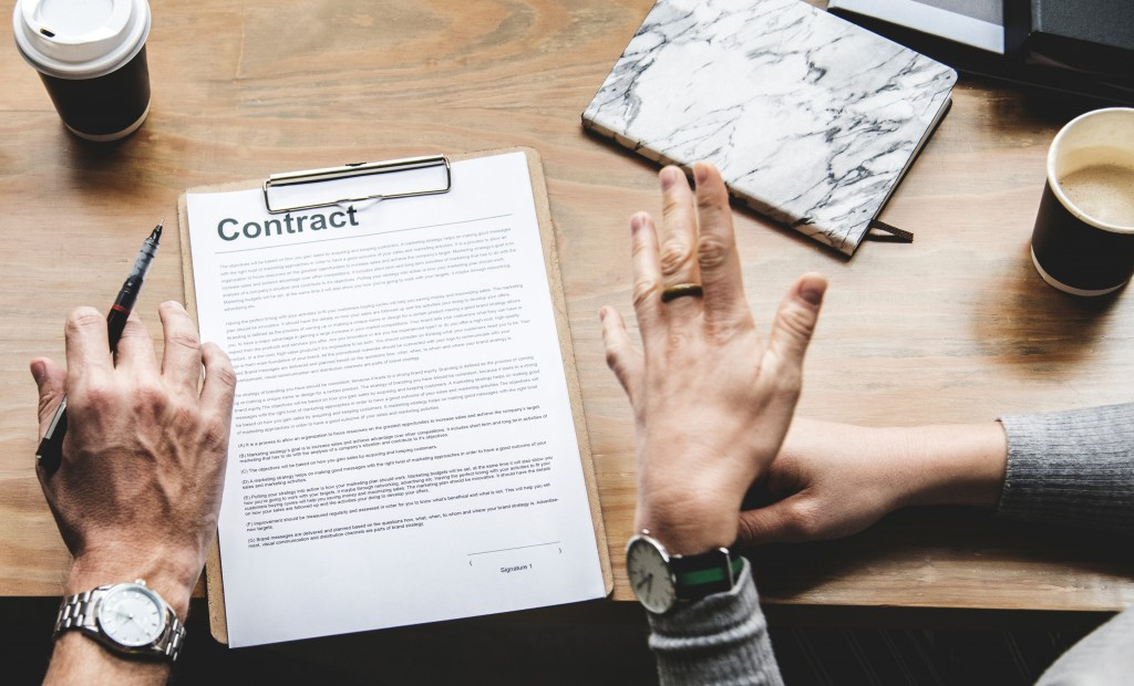 Advantages of digital signing - photo of contact on table with two people's hands, one holding a pen